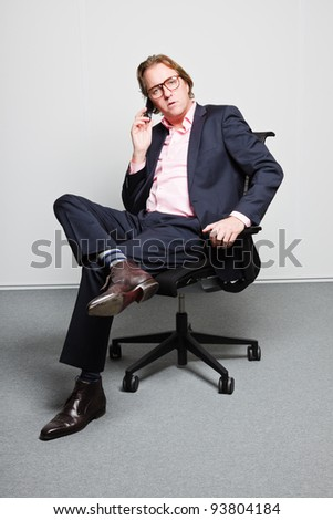 Young business man in office calling with cellphone wearing blue suit, pink shirt and glasses. - stock photo