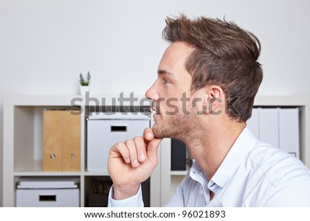 Young business man in profile view with hand on chin in office - stock photo