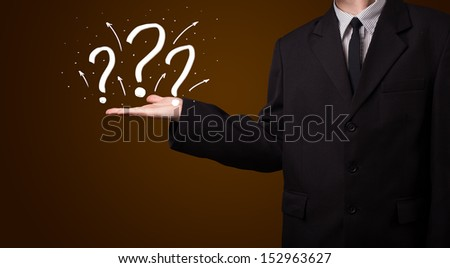 Young business man in suit presenting hand drawn question marks - stock photo