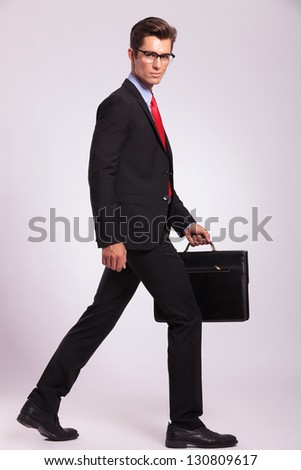 young business man is walking and looking at the camera while holding a suitcase . gray background - stock photo