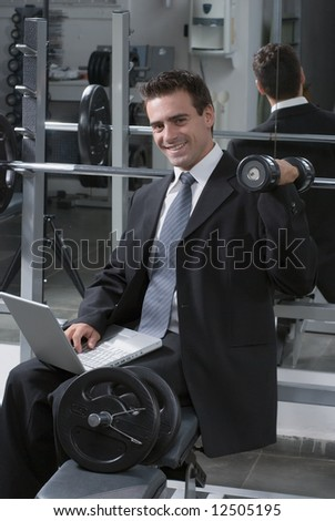 Young business man keeping himself fit while working - doing a shoulder press and smiling at the camera - stock photo