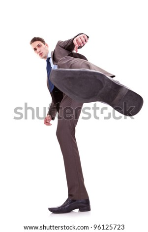 young business man kicking something on white background. wide angle shot, view from bellow - stock photo
