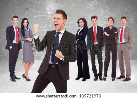 young business man leader screaming of joy in front of his successful team - stock photo