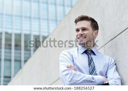 Young business man leaning against the wall, arms crossed - stock photo