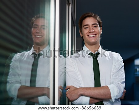 young business man leaning on office window with arms crossed and looking at camera smiling. Horizontal shape, front view, waist up - stock photo