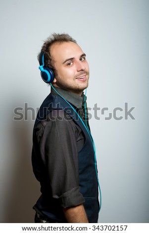 young business man listening to music on headphones, manager office concept, shot isolated on gray background - stock photo