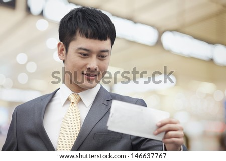 Young business man looking at flight ticket - stock photo