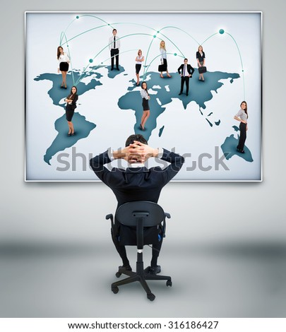 Young business man looking at network world map on wall - stock photo