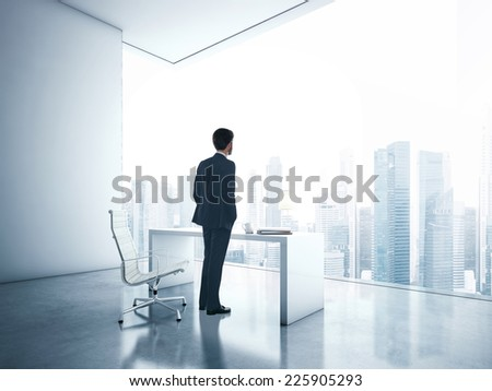 Young business man looking megalopolis through window - stock photo