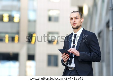 Young business man of arabic origin in a suit. Modern man in the background office building. Confident, charismatic modern business man. Man is holding an electronic tablet. Working out of the office. - stock photo