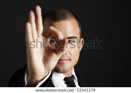 Young business man on black background looking thrue his fingers - stock photo