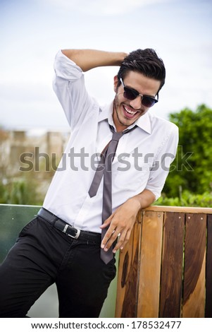 Young business man outdoors, looking casual and relaxed - stock photo