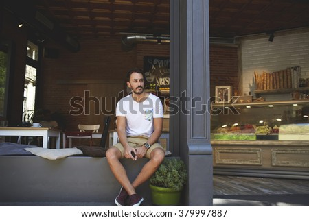 Young business man owner look away while sitting on windowsill of his restaurant in warm summer season, successful male entrepreneur dressed in casual clothes waiting for clients near grocery store    - stock photo
