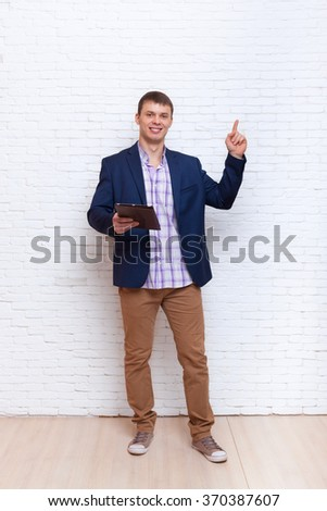 Young Business Man Point Finger To Copy Space Using Tablet Computer Over White Brick Wall - stock photo