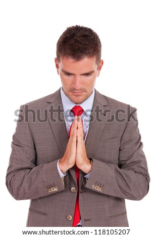 Young business man praying. Isolated against white background. - stock photo