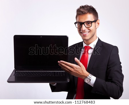 young business man presenting you with a new laptop - stock photo
