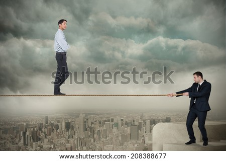 Young business man pulling a tightrope for businessman against balcony overlooking city - stock photo