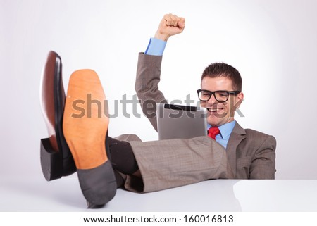 young business man reading something on his tablet and cheering while holding his feet on his desk. on a gray background - stock photo