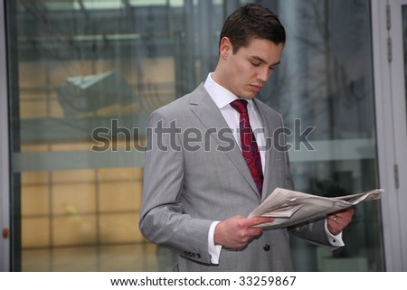 young business man reads newspaper - stock photo