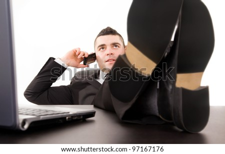 Young business man relaxing at office desk and talking on mobile phone, isolated on white - stock photo