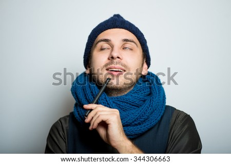 young business man remembers something or thinking with a pen, winter style clothes, studio shot isolated on the gray background - stock photo