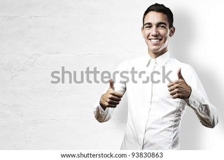 young business man satisfied against a white wall - stock photo