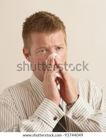 Young business man sick blowing nose on tissue - stock photo
