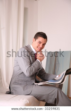 young business man sits an read newspaper - stock photo