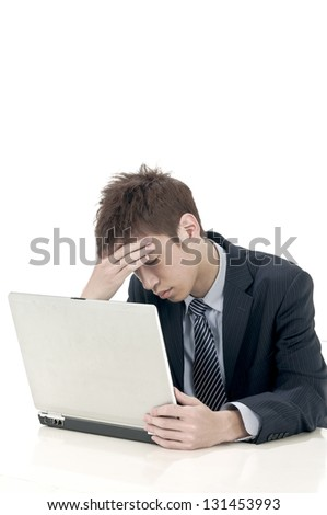 young business man sitting at the desk and looking baffled at his laptop - stock photo