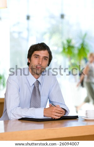 Young business man sitting behind a desk - stock photo