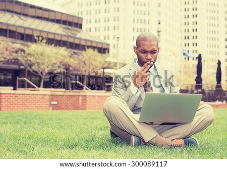 Young business man sitting on a lawn outside corporate office working on laptop computer  - stock photo