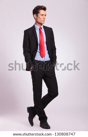 young business man standing with hands in his pockets and looking away from the camera, on gray - stock photo