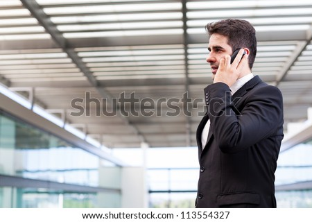 Young business man talking on cell phone at modern office - stock photo