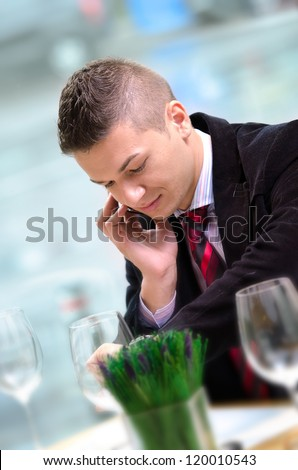 Young business man talking on the phone and looking at his watch - stock photo