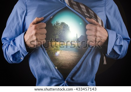 Young business man tearing his shirt off with a nature background, vacation or break concept - stock photo