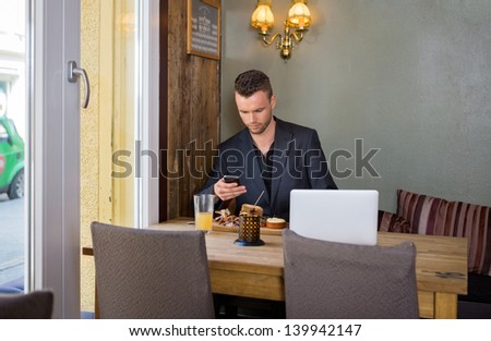 Young business man text messaging on cellphone while having food at restaurant - stock photo
