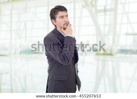 young business man thinking, at the office - stock photo
