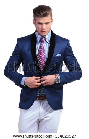 young business man unbuttoning his suit jacket while looking into the camera. on a white background - stock photo