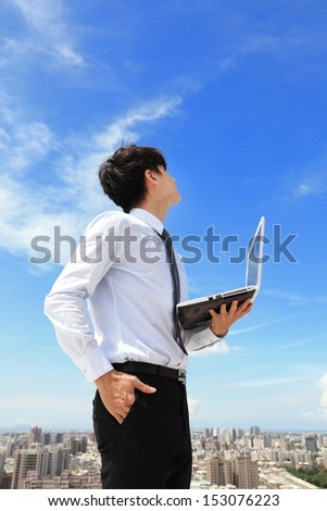 Young business man using laptop and look to blue sky and cloud with cityscape in the background, business and cloud computing concept - stock photo