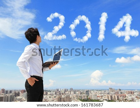 Young business man using laptop and look to 2014 year text with blue sky and cloud and cityscape in the background, business and cloud computing concept - stock photo