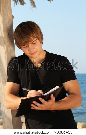 Young business man waiting for meeting, working with papers, outdoors - stock photo