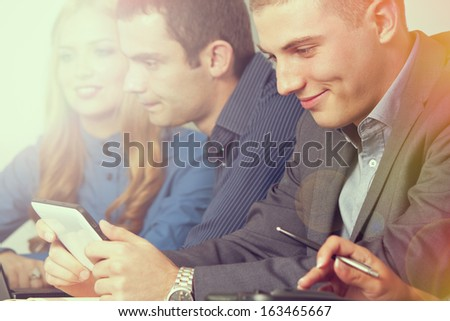 Young business man watching a tablet. Lens flare and light effect - stock photo