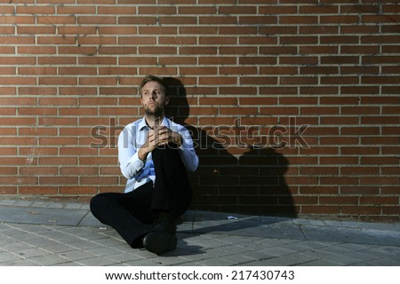 Young business man who lost job abandoned lost in depression sitting on ground street corner against brick wall suffering emotional pain, thinking and crying alone - stock photo