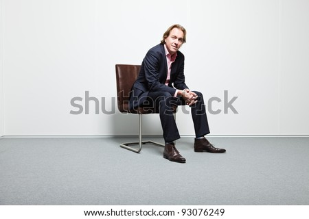 Young business man with blond hair in blue suit and pink shirt sitting on chair in office - stock photo