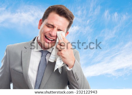 Young business man with grey suit over clouds background. Looking sad - stock photo