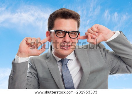 Young business man with grey suit over clouds background. Plugging his ears with his fingers - stock photo