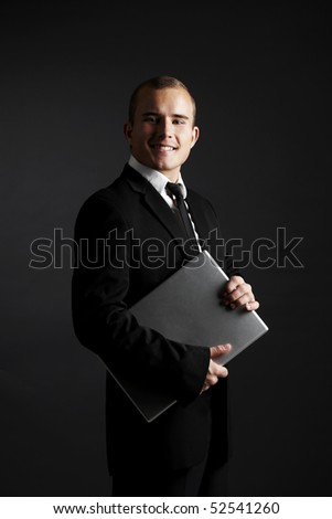 Young business man with laptop on black background - stock photo