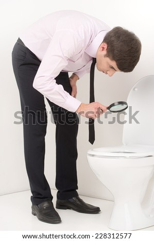 young business man with magnifying glass. guy looking at toilet seat through magnifying glass - stock photo