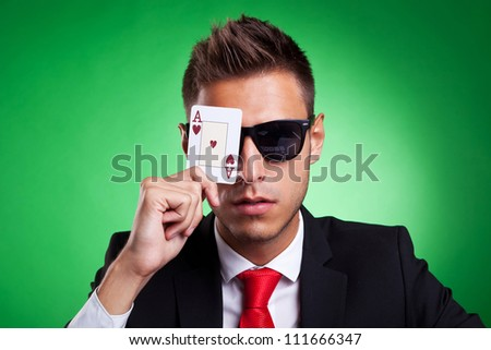 Young business man with sunglasses covers one eye with an ace of hearts. Over green background. - stock photo