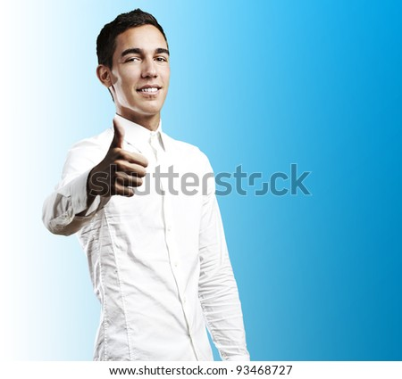 young business man with thumbs up against a blue background - stock photo